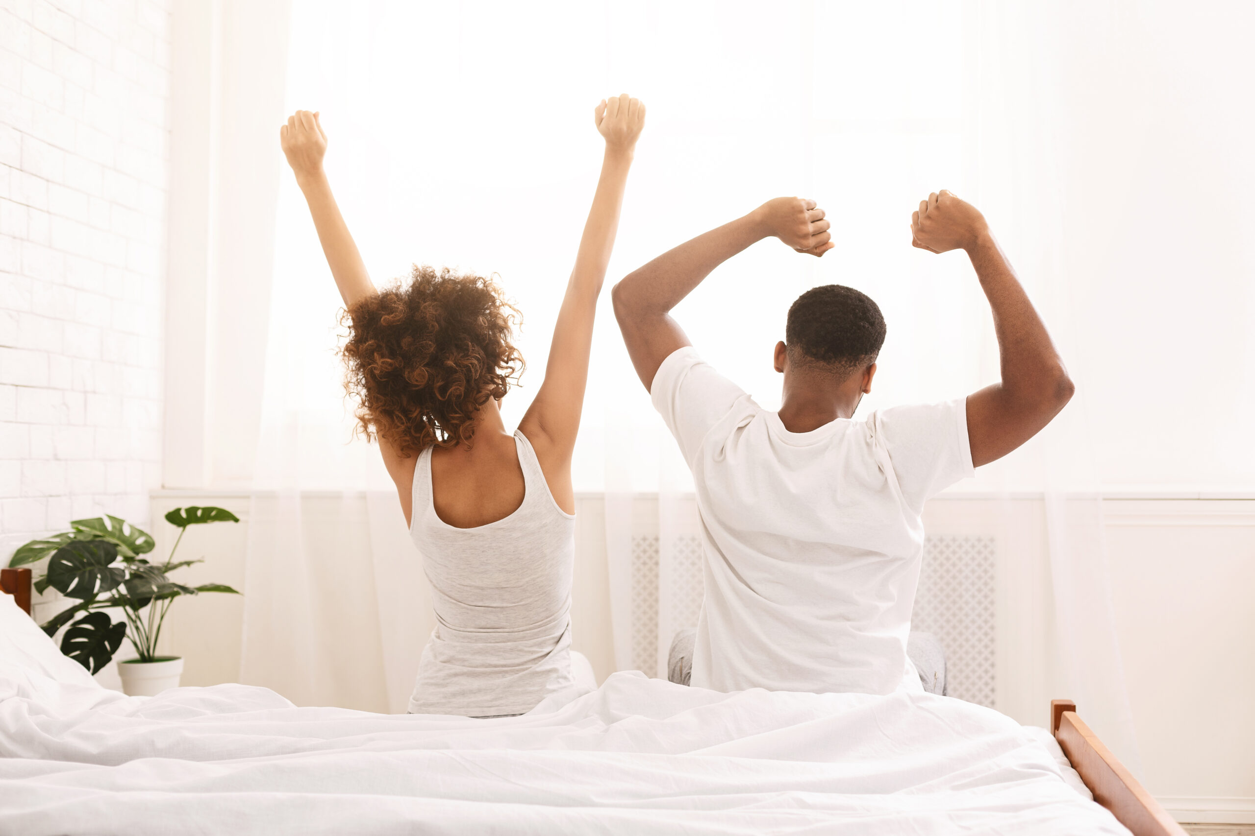 Happy,Black,Couple,Waking,Up,In,Morning,,Sitting,On,Bed,